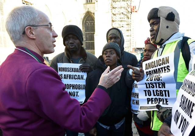 Anglican Archbishop Justin Welby of Canterbury, spiritual leader of the Anglican Communion, speaks with protesters on the grounds of England's Canterbury Cathedral, which was closed for a meeting of primates of the Anglican Church. (CNS/Reuters)