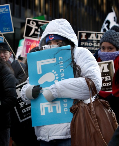 A woman tries to stay warm during Chicago's March for Life rally at Federal Plaza Jan. 17. Archbishop Blase J. Cupich of Chicago urged pro-life activists to call for reforms on the federal stage, framing abortion as a national issue in need of attention. (CNS/Karen Callaway, Catholic New World)