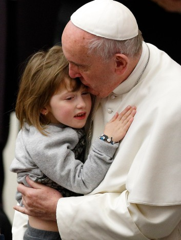 Pope Francis kisses a child while meeting the disabled during his general audience in Paul VI hall at the Vatican Jan. 20. (CNS/Paul Haring)