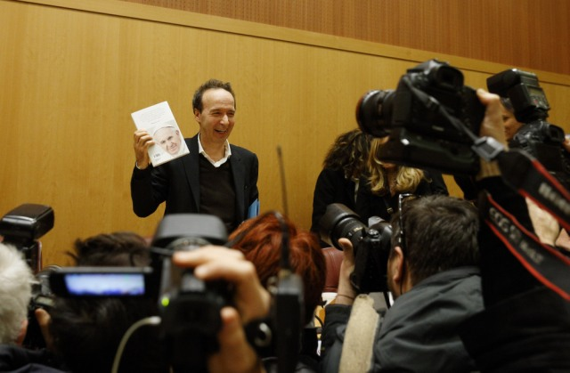 "Italian actor Roberto Benigni holds a copy of the book, ""The Name of God Is Mercy,"" during its presentation to journalists in Rome Jan. 12. (CNS/Paul Haring)"