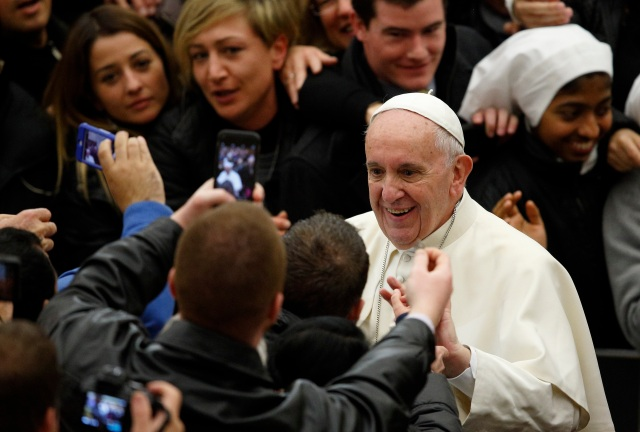 Pope Francis greets people as he leaves his general audience in Paul VI hall at the Vatican Jan. 13. (CNS photo/Paul Haring)