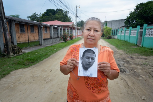 Vilma Maldonado holds a photo of her son, Jesus Humberto Sanchez Maldonado, in the street near her home in La Lima, Honduras, Dec. 16. The young man left for the United States in 2010, but Maldonado hasn't heard from him since his last phone call home in 2011 from the northern Mexican city of Monterrey. Maldonado is a member of a group of mothers of migrants who have disappeared on their journey north. (CNS photo/Paul Jeffrey)
