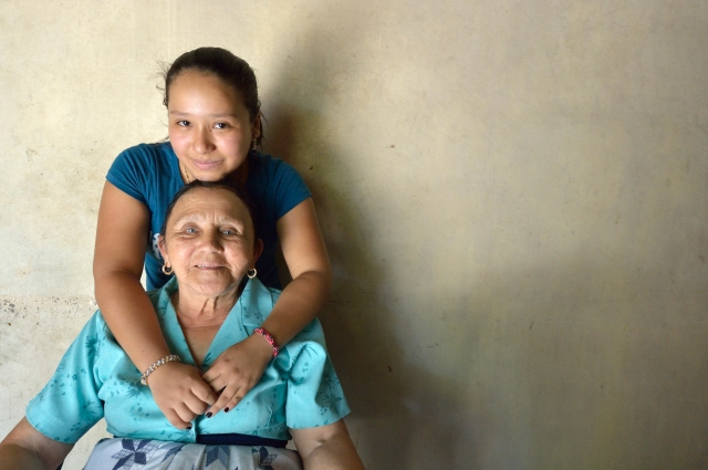 Aleska Garcia, 17, poses with her grandmother, Petronila Reyes, at their home in Goascoran, Honduras, Dec. 13. The teenager left Honduras in June 2014 to travel north to be with her mother, who has lived in the United States for 12 years, but she was detained by Mexican immigration officials and returned to Honduras. For now she says she wants to remain at home and finish her high school studies. (CNS photo/Paul Jeffrey)