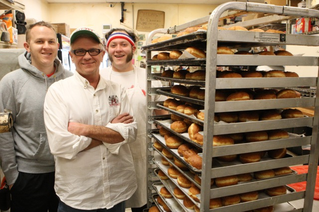 "Tim Kiedrowski, center, owner of Kiedrowski's Simply Delicious Bakery, with sons, Tim, left, and Michael, are shown with a rack of Polish-style doughnuts, known as ""paczki."" (CNS/Dennis Sadowski)"