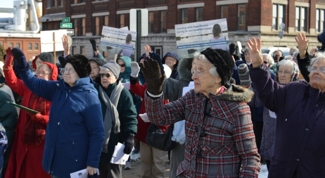 "Participants pray a silent blessing during a gathering in Dubuque for more than 20 billboards placed by women religious in strategic locations throughout Iowa, southwest Wisconsin and western Illinois. The billboards, posted in January and into February, carry the message ""Standing with Pope Francis; Caring for Our Common Home."" (CNS/Sister Carol Hoverman)"