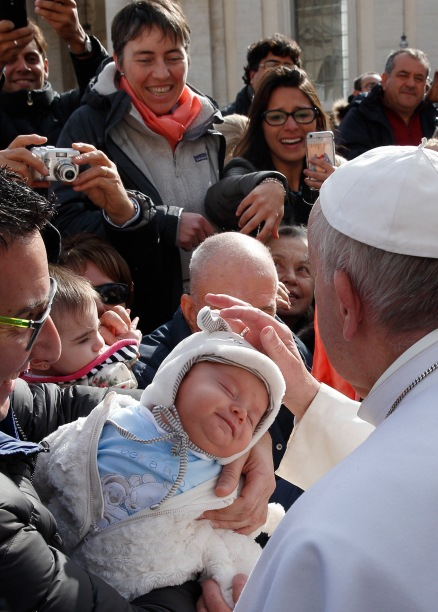 Pope Francis greets a sleeping baby as he leaves his general audience in St. Peter's Square at the Vatican Feb. 3. (CNS/Paul Haring)