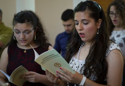 Parishioners at St. Sharbel Maronite Church, a mission chapel in Raleigh, N.C., attend the ordination of a subdeacon. The parish has welcomed many refugees from Iraq and Syria in recent years. (CNS/Chaz Muth)