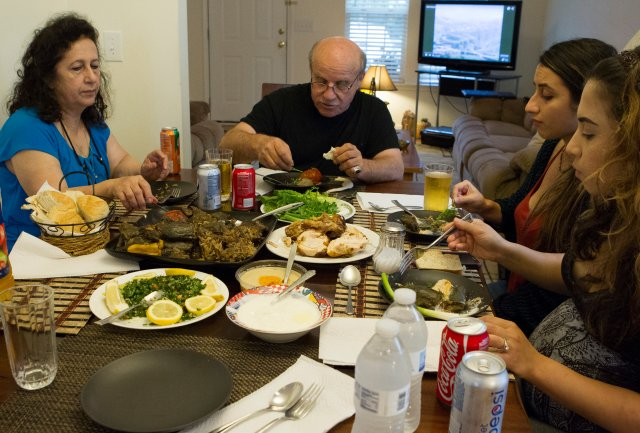 Iraqi refugee John Youkhanna and his family enjoy a traditional Middle Eastern meal at their home in Raleigh, N.C. (CNS/Chaz Muth)