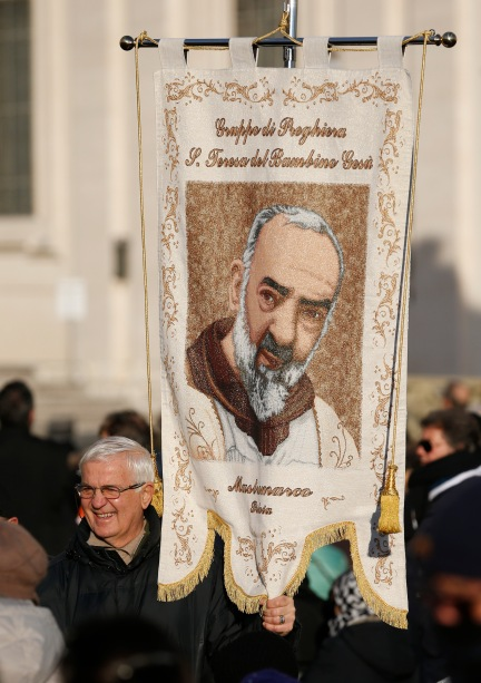A man holds a banner with an image of St. Padre Pio before Pope Francis' arrival for an audience with Padre Pio Prayer Groups from around the world in St. Peter's Square at the Vatican Feb. 6. The bodies of Padre Pio and St. Leopold Mandic were brought to Rome at the request of Pope Francis for the Year of Mercy. (CNS/Paul Haring)