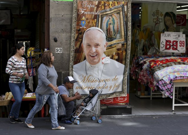 People walks past a Pope Francis banner outside a store in Mexico City Feb. 7. (CNS/Reuters)