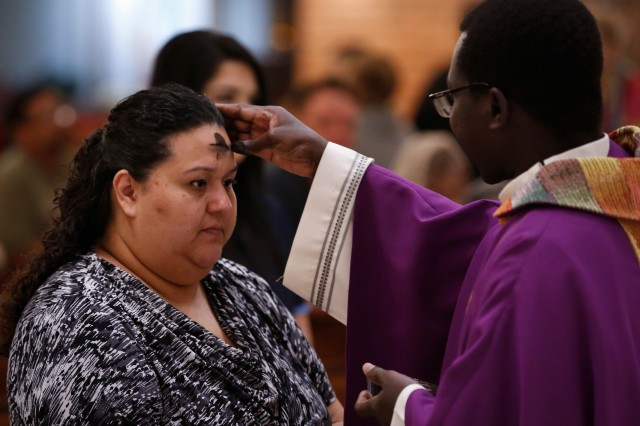 Father Mark Nyeko distributes ashes during Ash Wednesday Mass Feb. 10 at St. Helen Catholic Church in Glendale, Ariz. Ash Wednesday marked the start of Lent, a season of sacrifice, prayer and charity. (CNS/Nancy Wiechec)