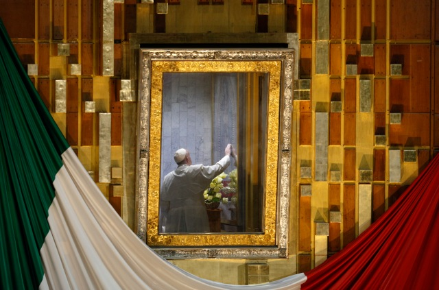 "Pope Francis touches the original image of Our Lady of Guadalupe after celebrating Mass in the Basilica of Our Lady of Guadalupe in Mexico City Feb. 13. The Marian image was rotated for the pope to pray in the ""camarin"" (""little room"") behind the main altar. (CNS/Paul Haring)"