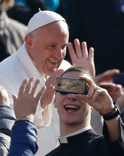 Seminarian Stephen Rooney of the Diocese of Rockville Centre, N.Y., takes a selfie as Pope Francis arrives to lead his general audience in St. Peter's Square at the Vatican Feb. 24. (CNS/Paul Haring)