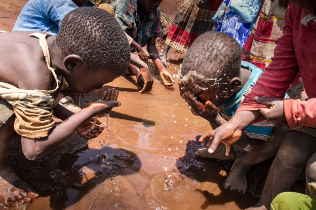 Refugee children wash their faces in a puddle in the refugee camp at Mwanza, Malawi, Feb. 8. (CNS photo/Erico Waga, EPA)