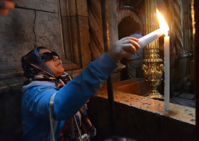 A woman lights a candle outside the Church of the Holy Sepulcher in Jerusalem's Old City in 2014. (CNS/Debbie Hill)