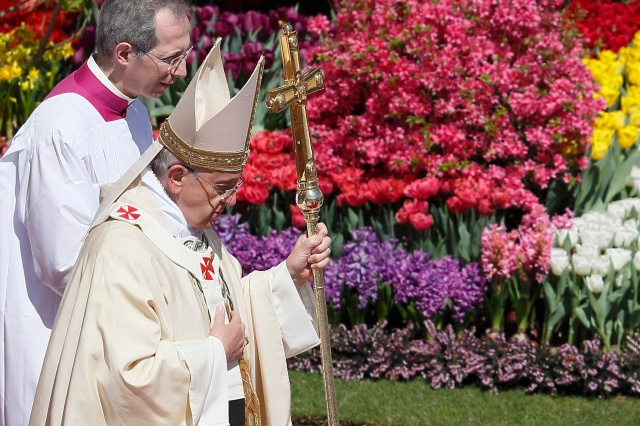 Pope Francis walks past flowers as he leaves after celebrating Easter Mass in St. Peter's Square at the Vatican in 2014. (CNS/Paul Haring)
