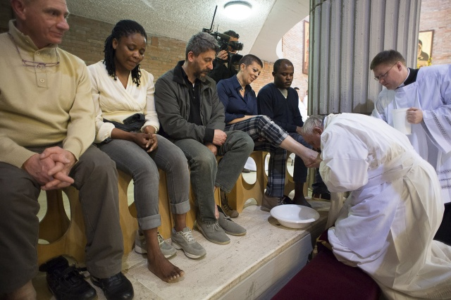 Pope Francis kisses the foot of a female inmate during the Holy Thursday Mass at Rebibbia prison in Rome last year. (CNS/L'Osservatore Romano)