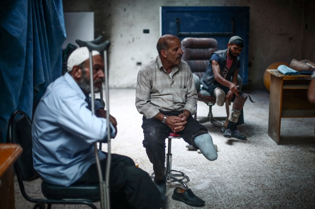 Syrian men who lost limbs during the civil war get prosthetic legs in Hamorya, Syria, in October. (CNS/EPA)