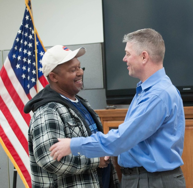 Deacon John Krenson, right, congratulates Bobby Kingfor completing the transitional housing program, finding a job and moving out on his own in Nashville, Tenn. (CNS/Theresa Laurence, Tennessee Register)