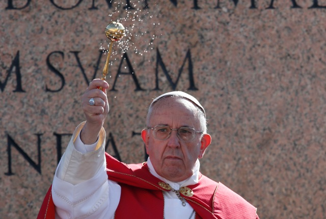 Pope Francis blesses with holy water as he leads a service at the obelisk at the beginning of Palm Sunday Mass in St. Peter's Square at the Vatican March 20. (CNS/Paul Haring)