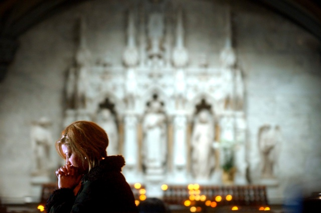 A woman prays at St. Patrick's Cathedral in New York. (CNS file/EPA)