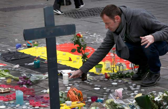 A man places flowers on a street memorial March 23 following bomb attacks in Brussels. (CNS/Reuters)