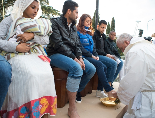 Pope Francis washes the foot of a refugee during Holy Thursday Mass of the Lord's Supper at the Center for Asylum Seekers in Castelnuovo di Porto, about 15 miles north of Rome. The pope washed and kissed the feet of refugees, including Muslims, Hindus and Copts. (CNS/L'Osservatore Romano)