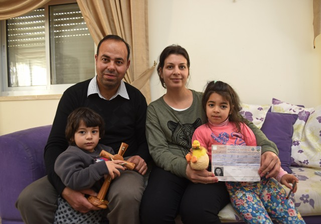 Nicola Sansour and his wife, Nivine, pose with two of their children, Elia, 2, and Rivana, 5, at their home in Beit Jalla. Nivine Sansour is holding her permit from the Israelis to travel to Jerusalem for Holy Week. (CNS/Debbie Hill)
