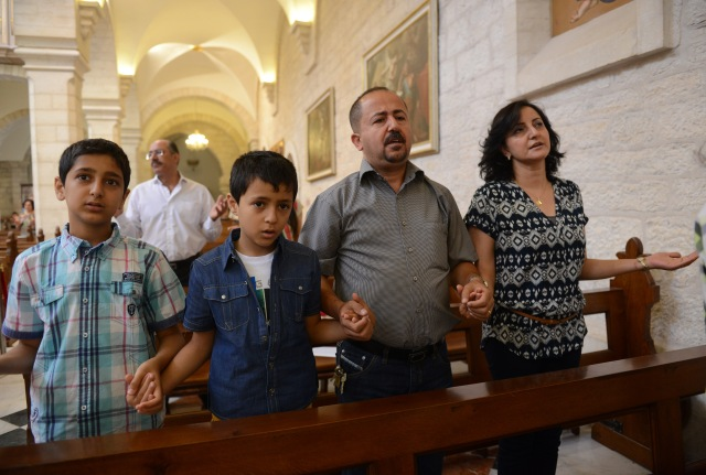 "A family prays in 2014 in the Church of St. Catherine in Bethlehem, West Bank. Pope Francis' apostolic exhortation on the family, ""Amoris Laetitia"" (""The Joy of Love""), was released April 8. (CNS/Debbie Hill)"