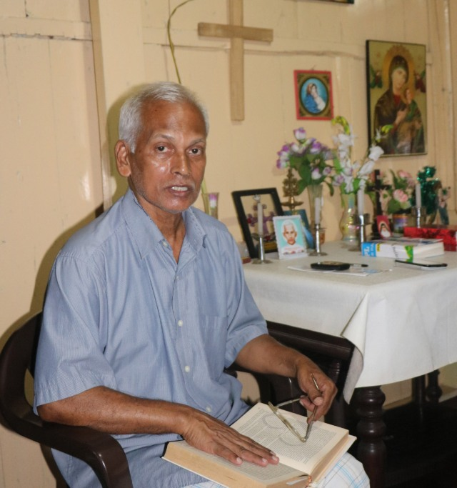 Mathew Uzhunnalil, brother of kidnapped Salesian Father Thomas Uzhunnalil, poses with his prayer book at his home in Ramapuram, India. (CNS/Anto Akkara)
