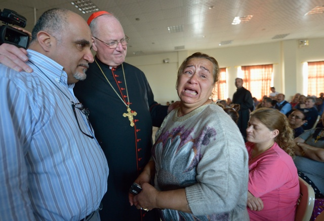 Cardinal Timothy M. Dolan of New York listens to Amal Mare during a visit to a camp for internally displaced families in Ankawa, Iraq, April 9. (CNS/Paul Jeffrey)