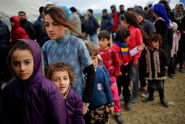 Young refugees wait in line for tea at a makeshift camp April 11 at the Greek-Macedonian border near the village of Idomeni, Greece. Pope Francis will travel to Lesbos, Greece, April 16. (CNS/Reuters)