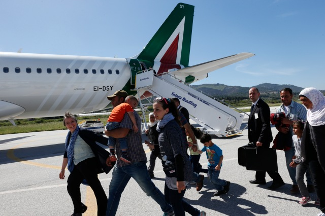 Refugees walk to board Pope Francis' plane to Rome at the international airport in Mytilene on the island of Lesbos, Greece, April 16. The pope brought 12 refugees to Italy aboard his flight. (CNS/Paul Haring)