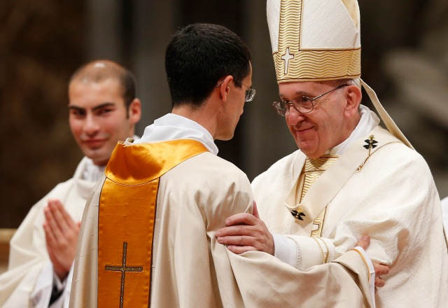 Pope Francis greets a new priest during the ordination Mass of 11 priests in St. Peter's Basilica at the Vatican April 17. Nine were ordained for the Diocese of Rome and two for the Rogationist religious order. (CNS/Paul Haring)