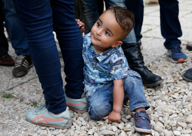 Syrian refugee Riad, 2, holds onto the leg of his mother, Nour, as she talks to media in Rome last April. The boy, his mother and his father, Hasan, were among 12 Syrian refugees that Pope Francis brought to Rome from a refugee camp in Greece last year. (CNS/Paul Haring)