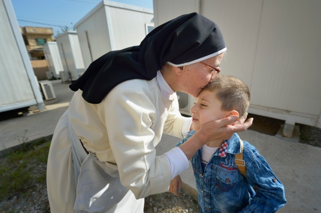 Dominican Sister Elene kisses 4-year old Luis Firas as he walks to a preschool in Ankawa, Iraq, April 7. The Dominican Sisters of St. Catherine of Siena were displaced by the Islamic State group in 2014 and have established schools and other ministries among the displaced. (CNS/Paul Jeffrey)