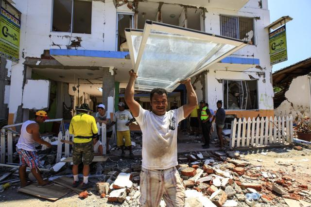 Residents recover some of their belongings April 25 from debris of a destroyed building in Canoa, Ecuador. Catholic agencies will begin building temporary shelters for thousands of families displaced by the April 16 magnitude-7.8 earthquake, the country's worst natural disaster in nearly seven decades. (CNS/EPA)