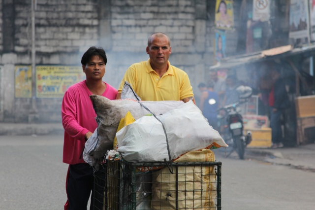 Mark Crosbie walks with Mel Macaereg in Manila, Philippines. Crosbie, an Irish Catholic street cleaner, was filmed for a job-swap TV documentary. (CNS/courtesy RTE)