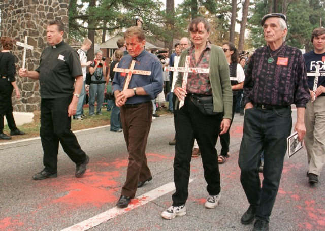 Jesuit Father Daniel Berrigan, right, and actor Martin Sheen, third from right, join the annual School of the Americas protest in 1999 at Fort Benning, Ga. (CNS/Liz Quirin, The Messenger)