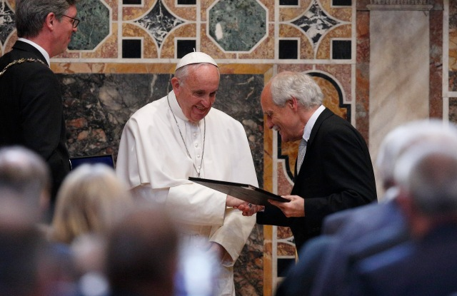 Pope Francis receives the Charlemagne Prize from Jurgen Linden, president of the Society for the Conferral of the Charlemagne Prize, during a ceremony in the Sala Regia at the Vatican May 6. At left is Marcel Philipp, mayor of Aachen, Germany, where the prize is normally presented. (CNS/Paul Haring)