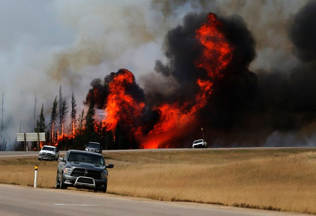 Smoke and flames from the wildfires erupt behind cars on the highway near Fort McMurray. (CNS/Reuters)