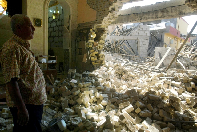 An Iraqi man inspects the damage in 2011 at a Catholic church after attacks in Kirkuk. (CNS/EPA)