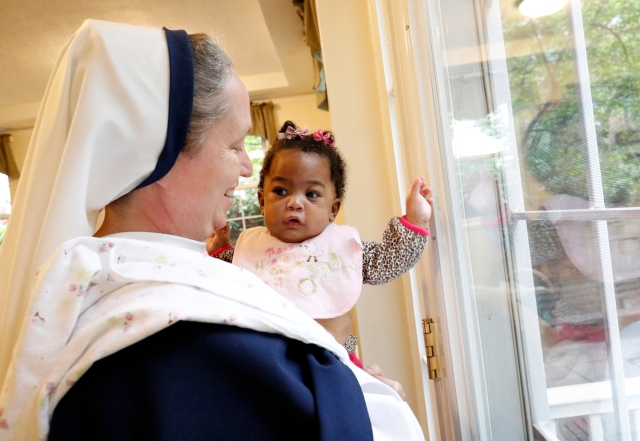 Sister Mary Elizabeth, vicar general of the Sisters of Life, holds six-month-old Esther May 4 at the religious community's Holy Respite residence in the Hell's Kitchen neighborhood of New York City. (CNS/Gregory A. Shemitz)