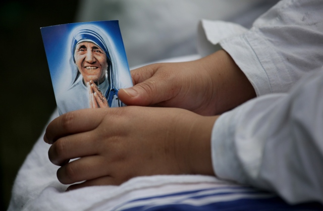 A nun from the Missionaries of Charity holds a picture of Blessed Teresa of Kolkata during a Mass to remember her in Kolkata, India, in 2011. (CNS/EPA)