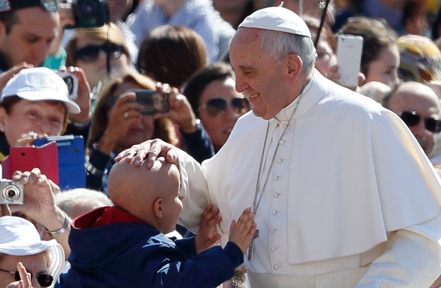 Pope Francis greets a child during his general audience in St. Peter's Square at the Vatican May 18. (CNS/Paul Haring)