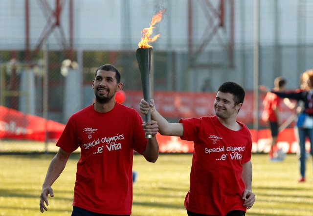 Salvatore Ruiu and Davide Paulis carry a torch during the opening ceremonies for the Special Olympics soccer tournament sponsored by the Knights of Columbus in Rome May 20. The tournament brought together players with and without intellectual disabilities as a model for how communities can include those with disabilities. (CNS/Paul Haring)
