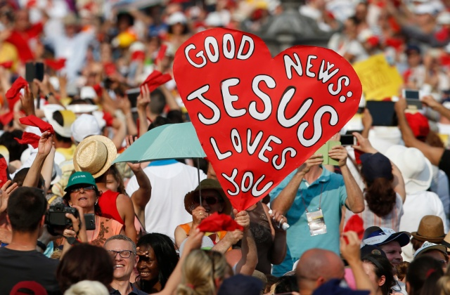 People hold signs as Pope Francis arrives to greet participants in the Renewal of the Spirit meeting in St. Peter's Square at the Vatican last summer. (CNS/Paul Haring)