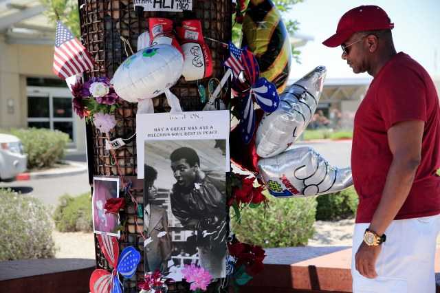 Jamie Rhodes of Indianapolis looks over a pop-up memorial to Muhammad Ali June 5 outside the Scottsdale, Ariz., hospital where Ali died June 3. (CNS/Nancy Wiechec)