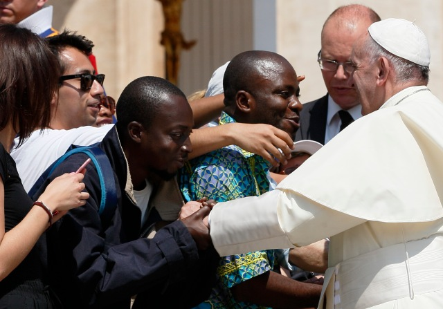 Pope Francis greets migrants during his general audience in St. Peter's Square at the Vatican June 8. (CNS/Paul Haring)