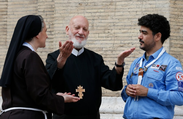 "Redemptorist Father Cyril Axelrod, who is deaf and blind, speaks to Franciscan Sister Veronica Donatello and scout Orazio Pemmisi, who is deaf, outside Chiesa Nuova in Rome June 10. The South African priest, who travels the world ministering to deaf Catholics, said that sign language, tactile sign language and body language are ""gifts of the Holy Spirit."" He was in Rome for the Year of Mercy jubilee celebration for the sick and persons with disabilities. (CNS/Paul Haring)"